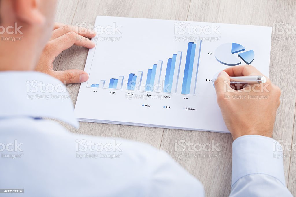 Businessman Analyzing Graph At Desk stock photo