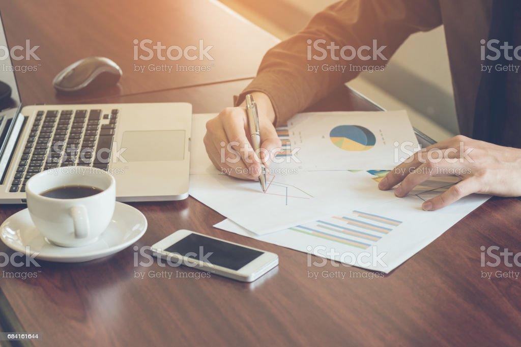 ビジネスマンがノート パソコンとオフィスでのコーヒーとグラフ ドキュメントを分析します。 ロイヤリティフリーストックフォト