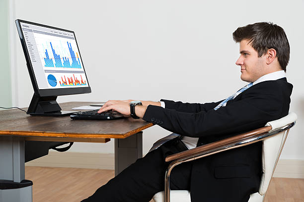 Businessman Analyzing Graph On Computer Young Businessman Leaning Back In His Chair While Analyzing Graph On Computer bad posture stock pictures, royalty-free photos & images