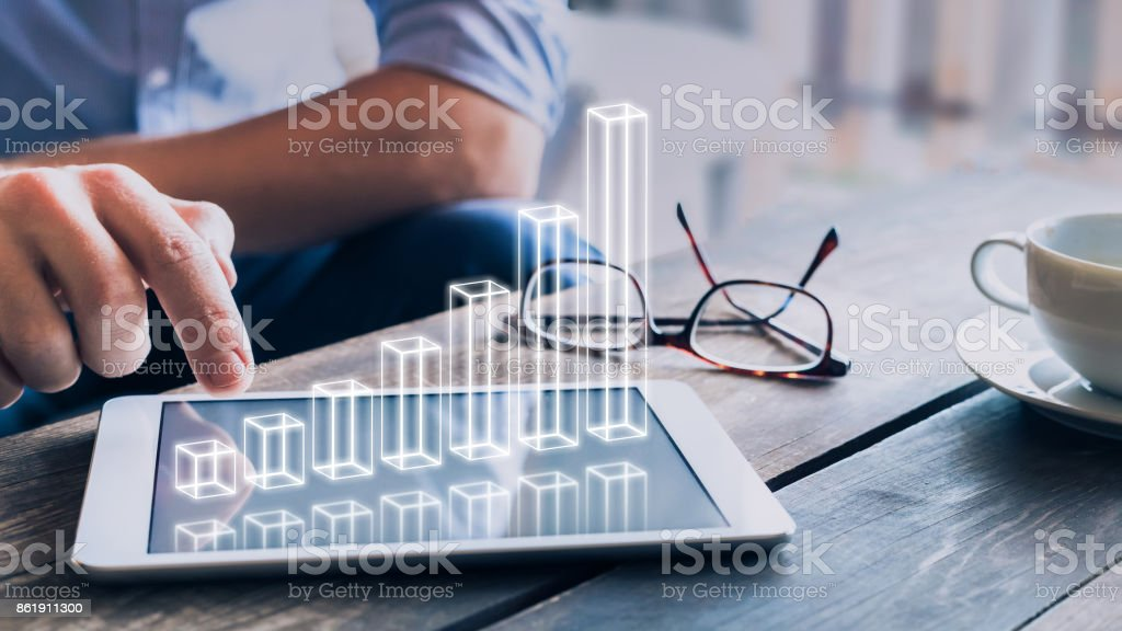 Businessman analyzing growing 3D AR chart above tablet computer screen stock photo