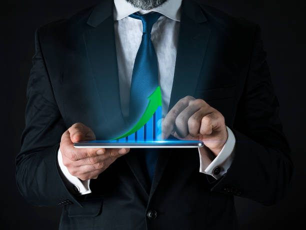 Businessman analyzing growing chart above digital tablet screen stock photo