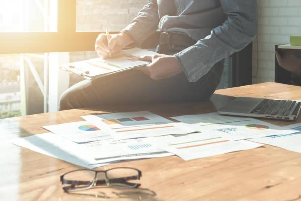 Homme d'affaires analyse graphiques d'investissement sur papier du document et l'utilisation d'ordinateur portable au bureau. Concept comptabilité statistique par rapport financier du revenu. effet de filtre vintage - Photo