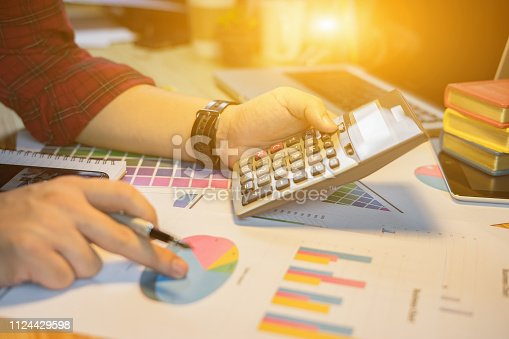 istock Businessman analyzing investment charts with calculator laptop. Accounting and technology in office.Business people using laptop at office,Analyze plans.selective focus,vintage color 1124429598