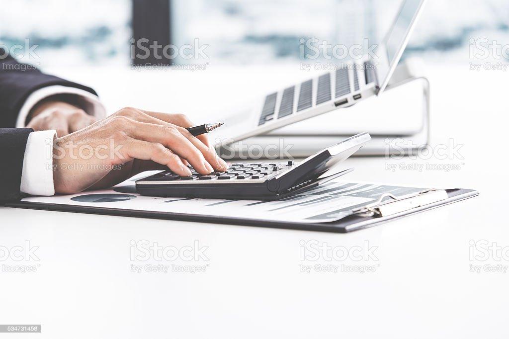 Uomo d'affari analizzando i grafici di investimento con computer portatile.   Contabilità  foto stock royalty-free