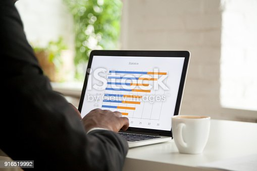 istock Businessman analyzing project statistics graph on laptop screen, close up 916519992