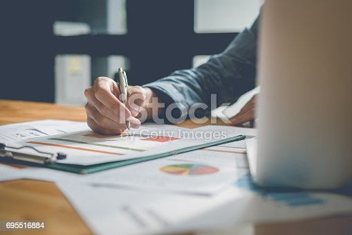 istock Businessman analyzing report on chart with laptop computer in office 695516884