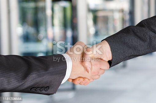 istock A businessman and a businesswoman are shaking hands. 1131208554