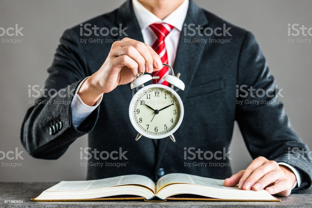 Businessman and alarm clock,studio shooting stock photo