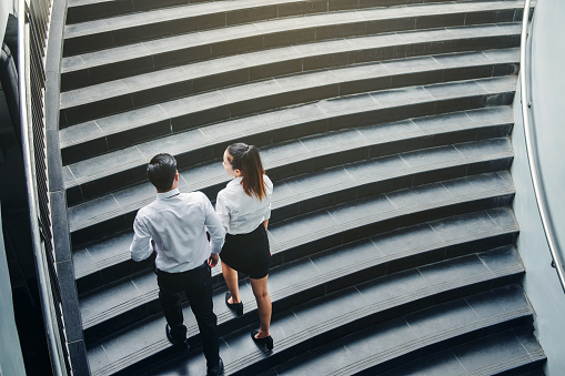 684803840 istock photo Businessman and Business woman go up the stairs Success concept 840574584