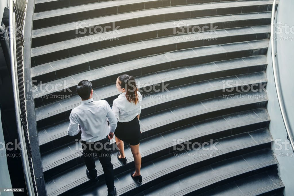 Businessman and Business woman go up the stairs Success concept stock photo