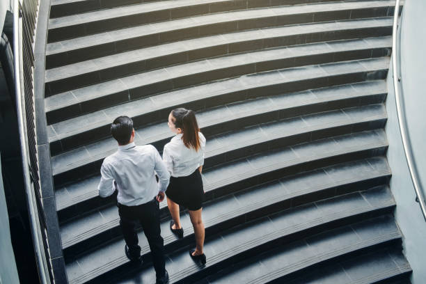 businessman and business woman go up the stairs success concept - staircase stock photos and pictures