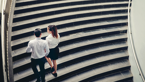 684803840 istock photo Businessman and Business woman go up the stairs Success concept 876460242