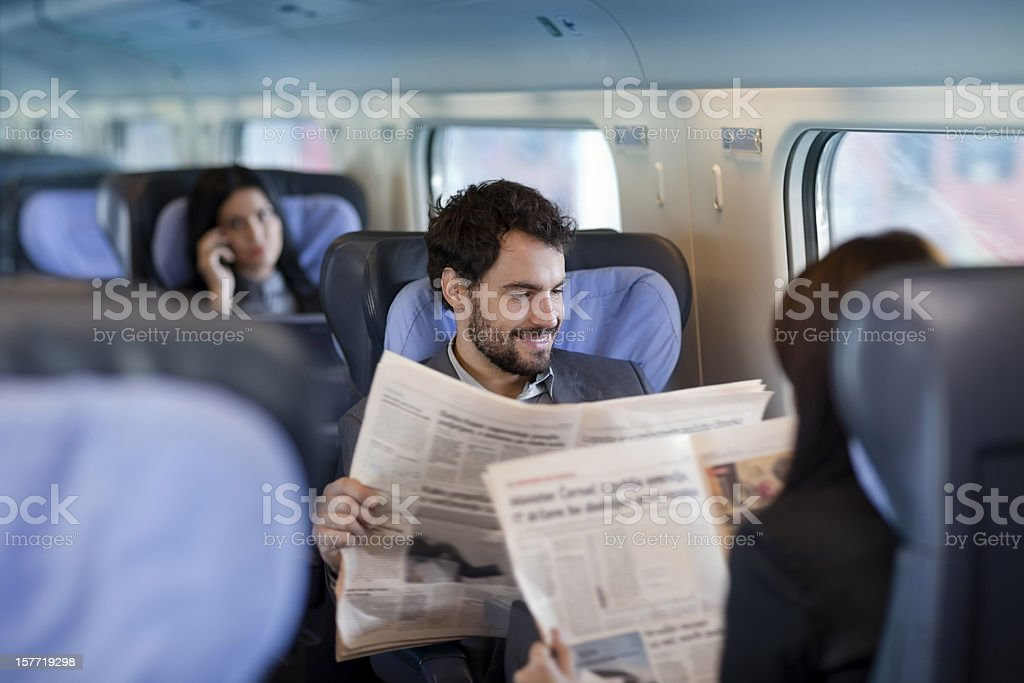 Businessman and business woman  reading  Newspaper  on a Train stock photo