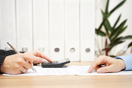 istock businessman and businesswoman are analyzing financial numbers on document 481326436