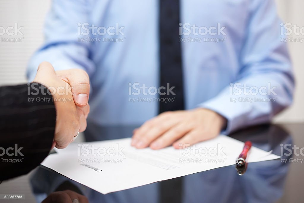 Businessman and businesswoman are handshaking over signed contract, partnership concept stock photo