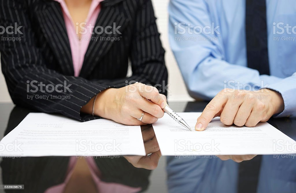 businessman and businesswoman are pointing to .article of the treaty stock photo