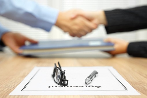 istock businessman and businesswoman are shaking hands and exchanging folder 512154742