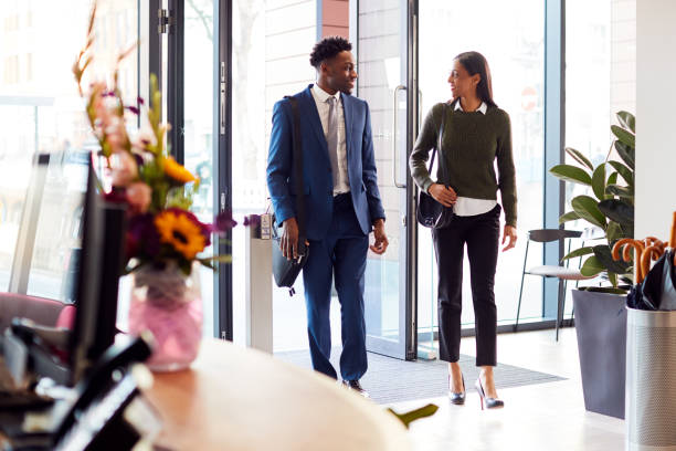 Businessman And Businesswoman Arriving For Work At Office Walking Through Door Businessman And Businesswoman Arriving For Work At Office Walking Through Door arrival stock pictures, royalty-free photos & images
