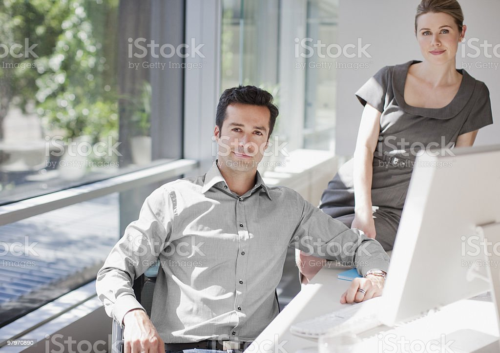 Businessman and businesswoman at computer in office royalty-free stock photo