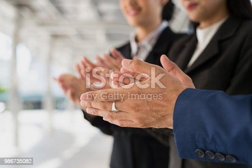 924520168 istock photo businessman and businesswoman clap their hands to congratulate the signing of an agreement or contract between their companies. success, greeting and partner concept. 986735082