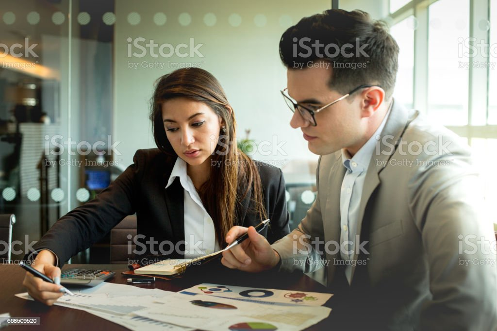 Businessman and businesswoman discuss together about there business performance. – zdjęcie