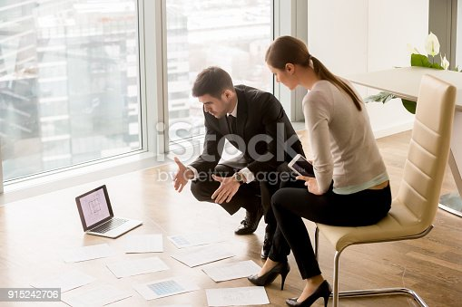 istock Businessman and businesswoman discussing interior design, planning new building project 915242706