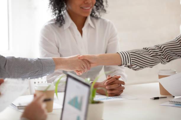 Empresario y empresaria apretón de manos en reunión de grupo diverso, de cerca - foto de stock