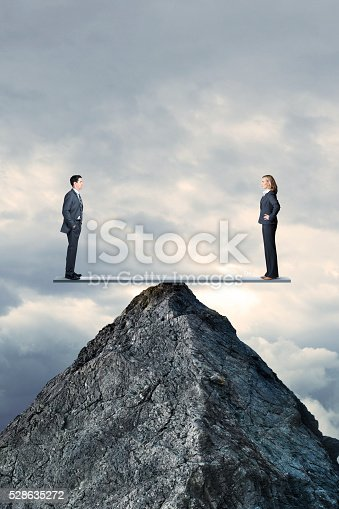 A businessman and a businesswoman  maintain their balance on a seesaw that is perched high on the pinnacle of a mountaintop. They face each otheras they maintain perfect balance and equality.