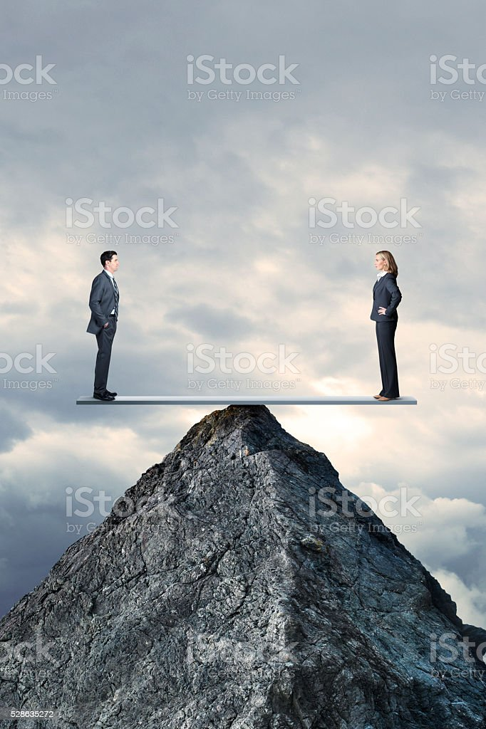 Businessman And Businesswoman In Perfect Balcance On Seesaw On MountaintopBusinessman And Businesswoman stock photo