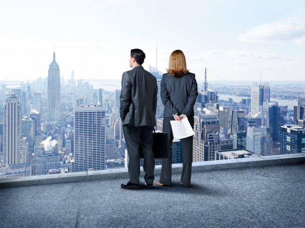 Businessman And Businesswoman Look Out Over The New York City Skyline stock photo