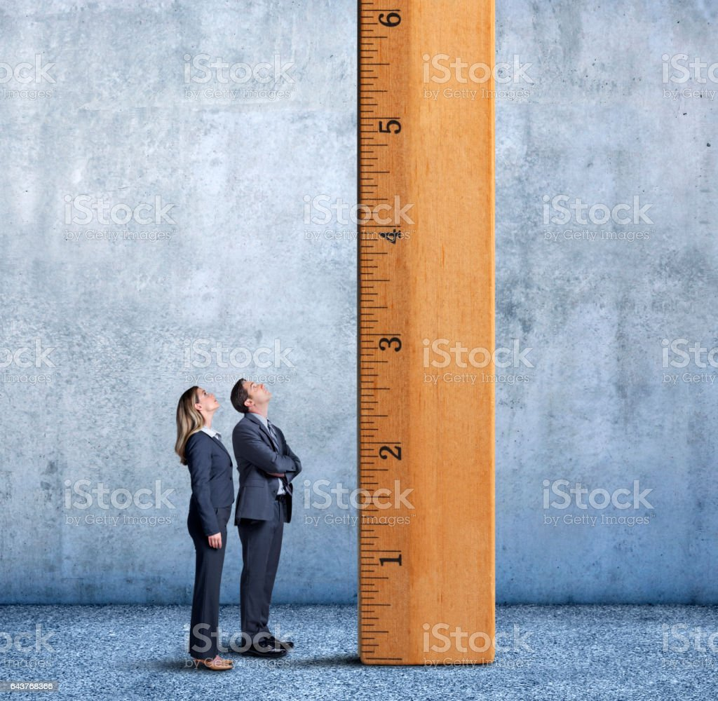 Businessman And Businesswoman Looking Up A Tall Ladder stock photo