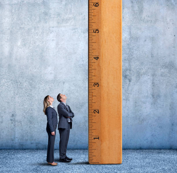 businessman and businesswoman looking up a tall ladder - measuring stock photos and pictures