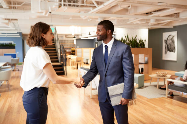 Businessman And Businesswoman Meeting And Shaking Hands In Modern Open Plan Office stock photo