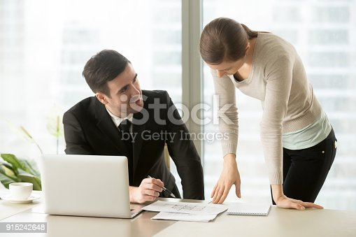 915688450istockphoto Businessman and businesswoman negotiating over building plan, discussing house project 915242648