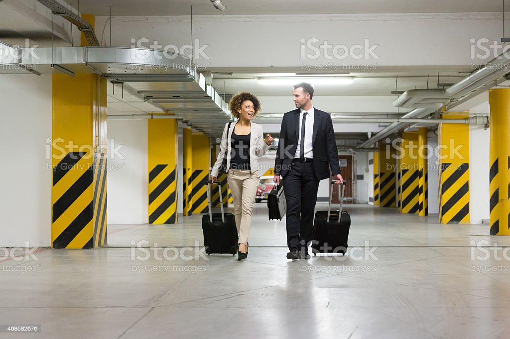 Businessman and businesswoman on business travel Businessman and afro american wearing formal outfits walking in the underground parking and carrying suitcases.  2015 Stock Photo