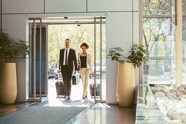 businessman and businesswoman on business travel - entrance stock photos and pictures
