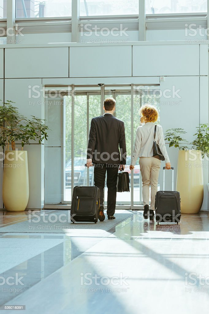 Businessman and businesswoman on business travel Back view of businessman and businesswoman walking on the hotel hall and carrying suitcases.  2015 Stock Photo