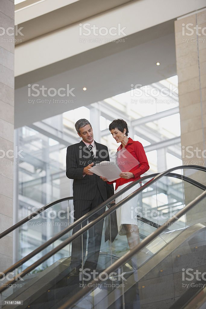 Businessman and businesswoman on escalator royalty-free stock photo