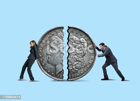 A businesswoman uses her back and a businessman leans into a silver dollar that is broken in half as they attempt to do some financial repair isolated on a blue background.