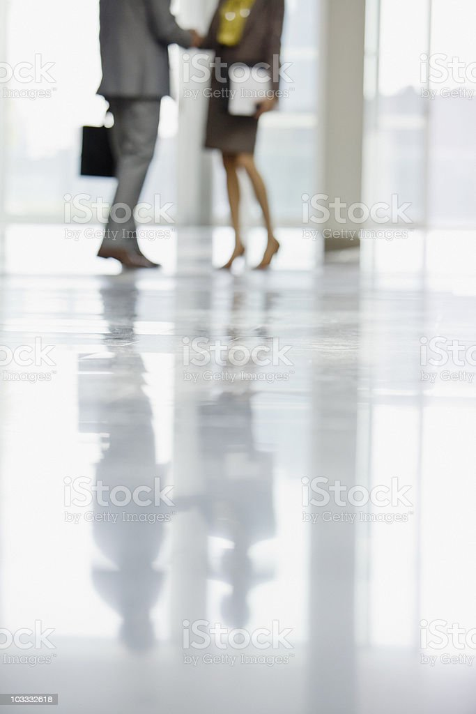 Businessman and businesswoman shaking hands in lobby royalty-free stock photo