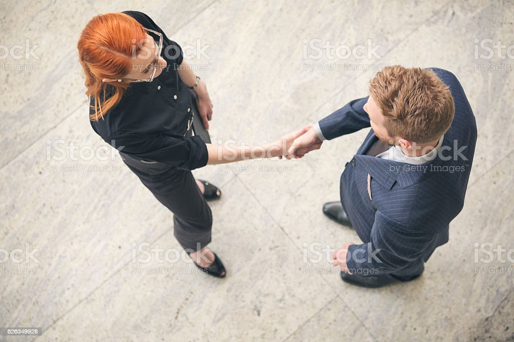 Businessman and businesswoman shaking hands in the lobby overhea stock photo