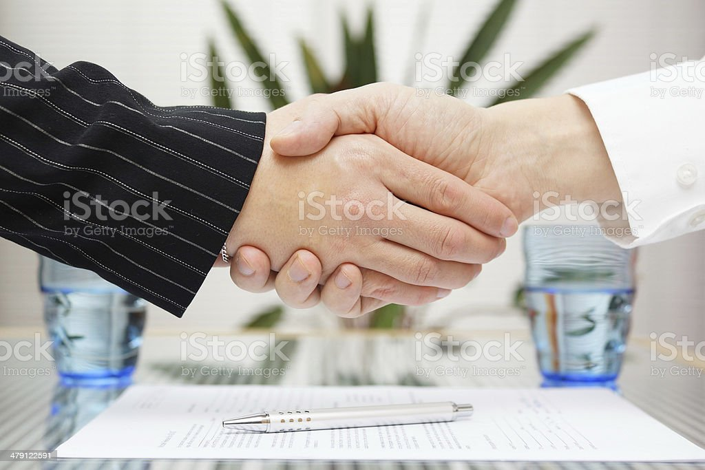 businessman and businesswoman shaking hands over signed contract. stock photo