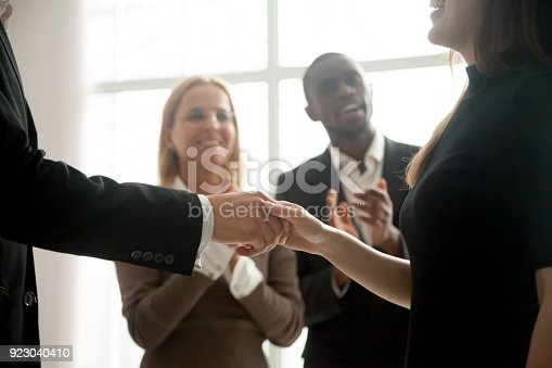 923041456 istock photo Businessman and businesswoman shaking hands with people applauding at background 923040410