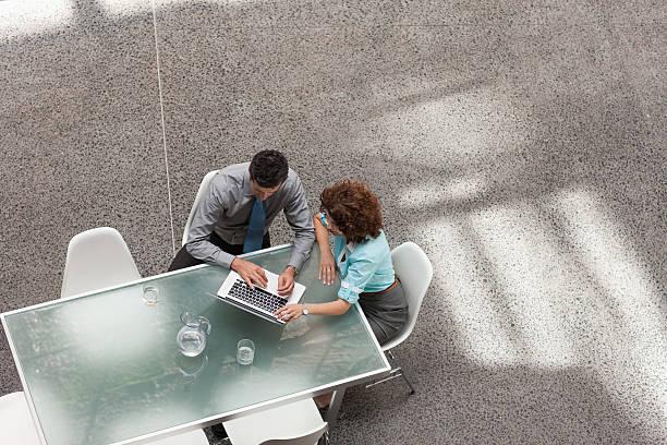 uomo d'affari e donna d'affari condivisione di computer portatile al tavolo - business meeting, table view from above foto e immagini stock