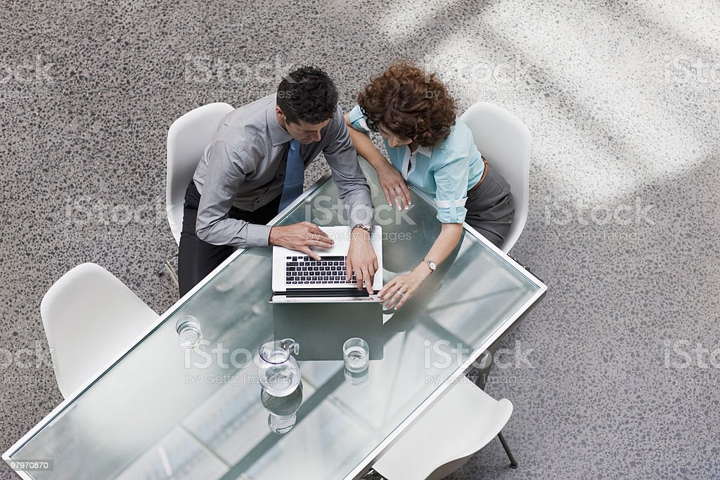 Businessman and businesswoman sharing laptop at table royalty-free stock photo