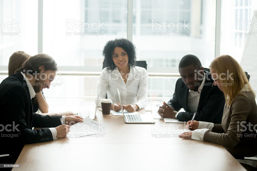 Businessman and businesswoman signing contracts at group multiracial meeting stock photo