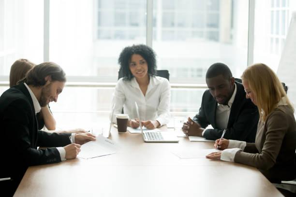 Empresario y empresaria, firma de contratos en la reunión del grupo multirracial - foto de stock