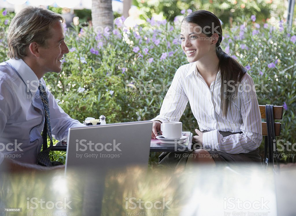 Businessman and businesswoman sitting at a patio table with laptop royalty-free stock photo