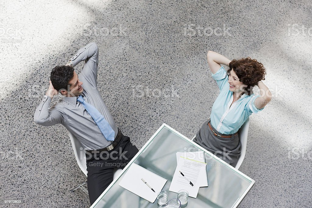 Businessman and businesswoman sitting with hands behind heads royalty-free stock photo