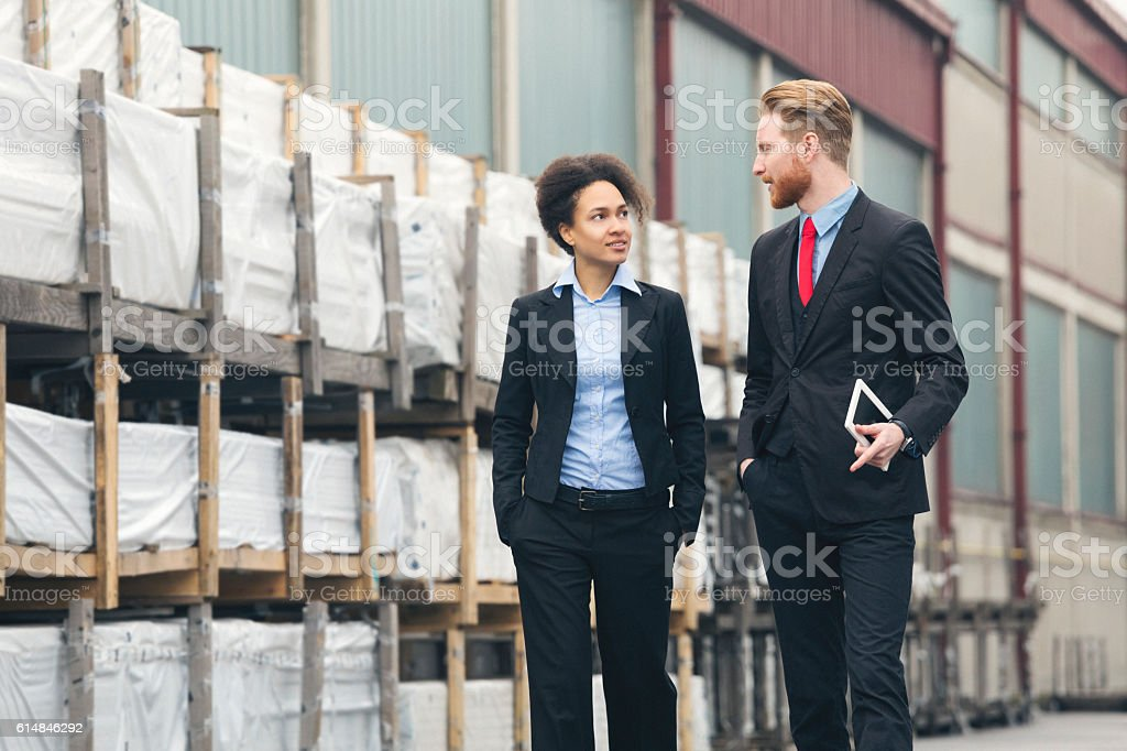 Businessman and businesswoman speaking near storage stock photo